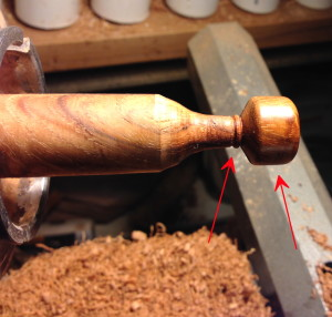 Turned knob, still attached to blank in lathe. Red arrows point to the knob and to the parting point.