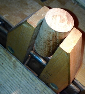 Shortened cylinder held in setup, to pare cut end smooth.