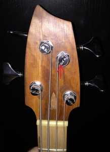 Bass headstock with strings attached. Note: the red arrow is pointing towards the hole down in the tuner, and you can see the string coming up from that point.