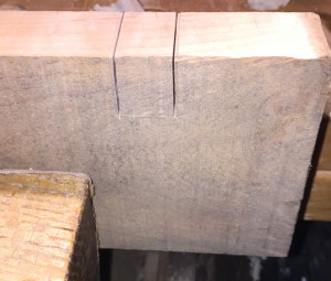 Marks from cross piece, with saw kerfs next to them.