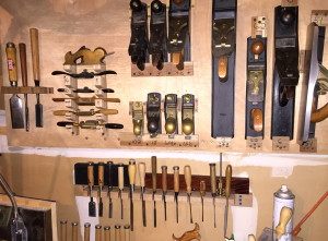 Large rack with all of the intended chisels in place (including Auriou Model Maker's rasp in far right position), as well as winding sticks (right) and micrometer w/case (left), behind chisel handles.