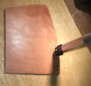 Thonging tool with three-chisel head, with the chisels driven through the leather side.
