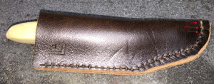 Completed knife sheath, with visible damage from the shoulder of the thonging chisel.