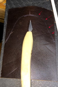 Knife laid on leather blank, with pattern drawn onto leather with white-lead pencil.